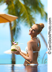 Smiling woman tholding a tropical cocktail