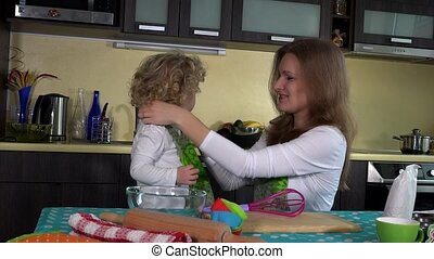 Smiling woman tie apron on little girl near kitchen table....