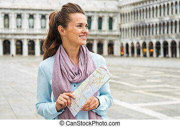 Smiling woman tourist holding map in empty St. Mark's Square...