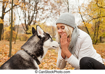 Smiling woman training dog husky outdoors in the autumn park