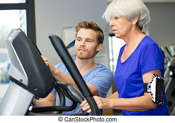 smiling woman training on machines in gym
