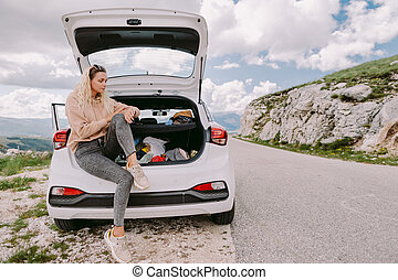 smiling woman travel by car in mountains