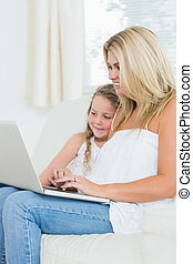Smiling woman typing on notebook while her daughter is sitting next to her