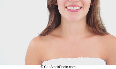 Smiling woman using a cotton pad on her face