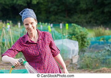 Smiling woman using a garden hose nozzle