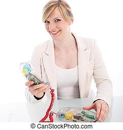 Smiling woman using a landline telephone