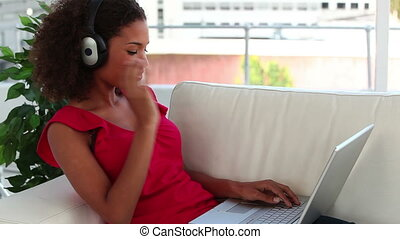 Smiling woman using a laptop while listening to music