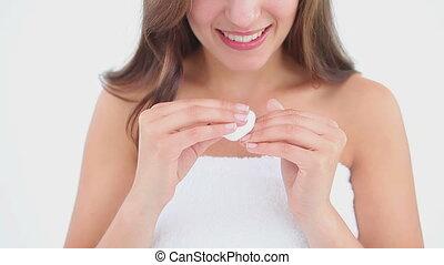 Smiling woman using a nail polish remover