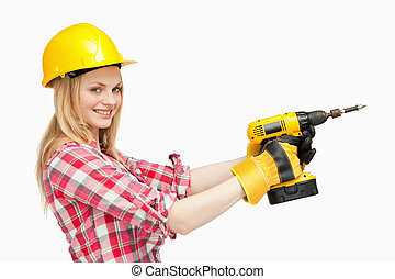 Smiling woman using an electric screwdriver