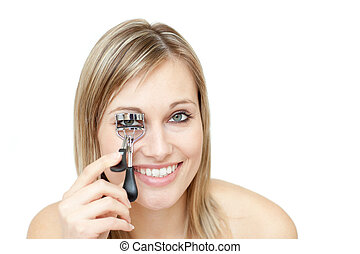 Smiling woman using an eyelash curler