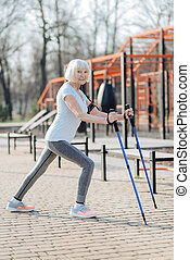 Smiling woman using crutches while exercising