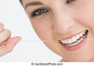 Smiling woman using dental floss against the white ...