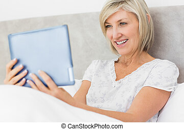 Smiling woman using digital tablet in bed