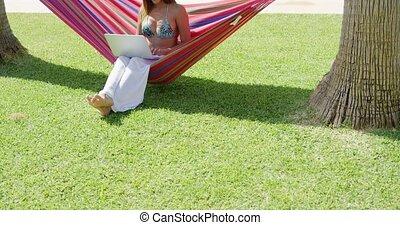 Smiling woman using laptop in hammock