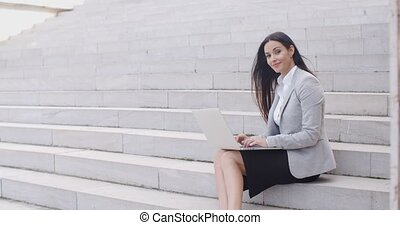 Smiling woman using laptop on stairs