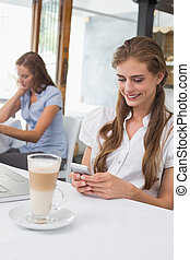 Smiling woman using mobile phone in coffee shop