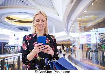 Smiling woman using mobile phone in shopping mall