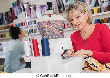 smiling woman using sewing machine