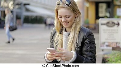 Smiling woman using smartphone on street
