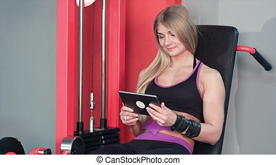 Smiling woman using tablet while doing leg exercises in the gym