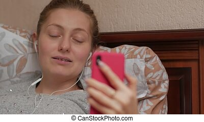 Smiling woman video call focus transition closeup smartphone with headphones in the bed caucasian white 30 years old