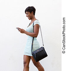 Smiling woman walking and reading text on mobile phone