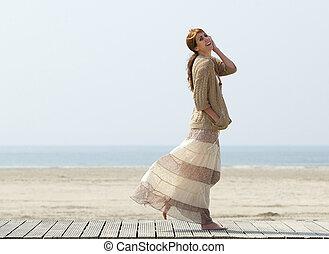 Smiling woman walking at the beach
