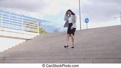 Smiling woman walking down staircase - Smiling young...
