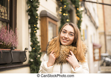 Smiling woman walking in city, beautifully decorated for the Christmas