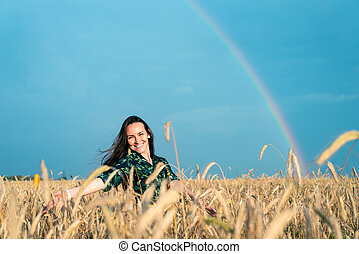 Smiling woman walking on a wheat field with his hands on the spikes on the background of the rainbow