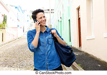 Smiling woman walking on street with cellphone and bag