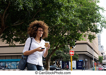 Smiling woman walking with mobile phone in the city