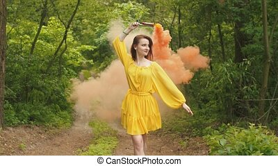 Smiling woman walking with smoke bomb in forest - Charming...