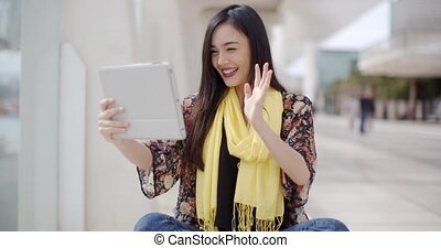 Smiling woman waving at her tablet computer - Smiling...
