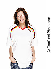 smiling woman wearing football shirt with hands in her pockets on white background