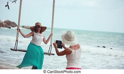 Smiling woman wearing hat taking photo with phone her friend on a swing at beach. Young happy smiling girls having fun on a swing on a tropical beach. 1920x1080