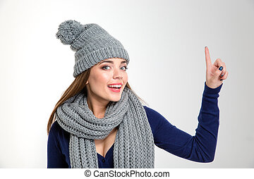 Smiling woman wearing in scarf and hat pointing finger up
