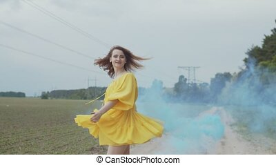 Smiling woman whirling in color smoke among field - Portrait...