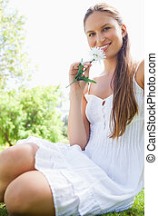Smiling woman with a flower sitting on the lawn