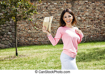 Smiling woman with a hat in the park