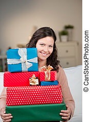 Smiling woman with a stack of gift boxes
