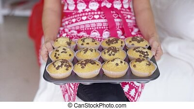 Smiling woman with a tray of freshly baked cakes