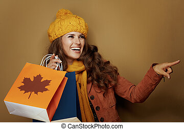 smiling woman with autumn shopping bags pointing at ...