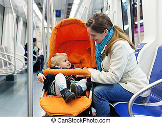 woman with baby in stroller at subway