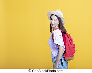 smiling woman with backpack standing on yellow background