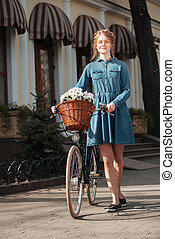 Smiling woman with bicycle walking outdoors