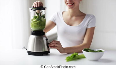 smiling woman with blender and green vegetables