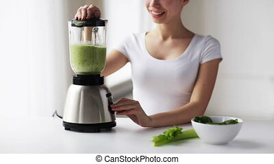 smiling woman with blender and green vegetables - healthy ...