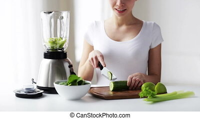 smiling woman with blender chopping vegetables