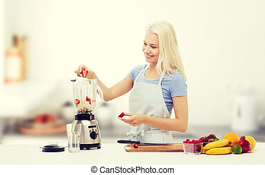 smiling woman with blender preparing shake - healthy eating,...